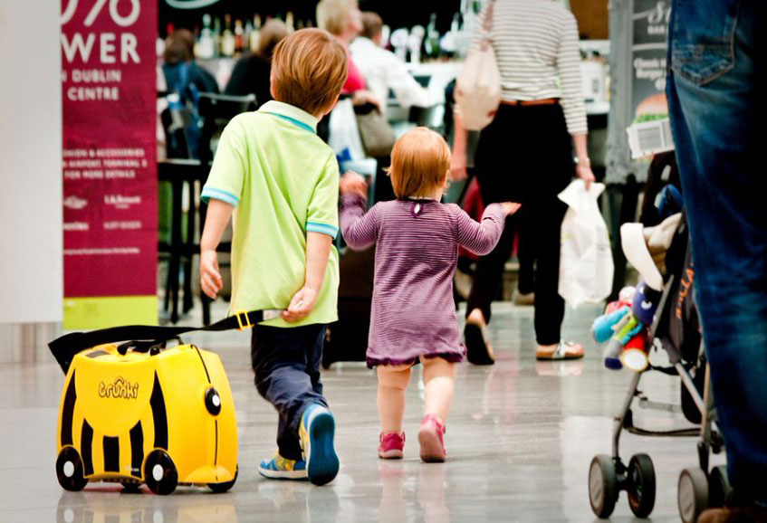 toddlers with suitcase travelling with children