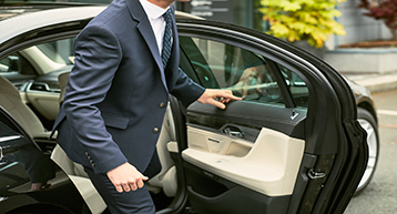 Businessman getting out of car out side Platinum Services